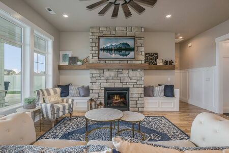 Beautiful blue rug and stone fireplace in great room of open floorplan house