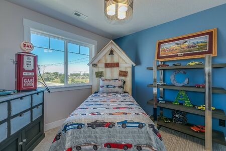 Boys bedroom with blue walls and a car theme throughout