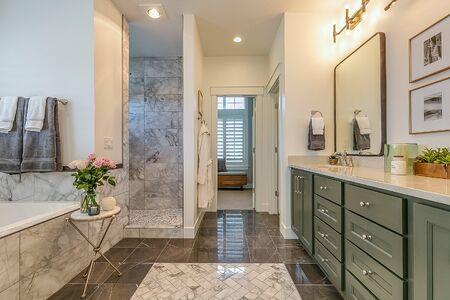 Lovely dark green bathroom cabinets in spa-like master bathroom