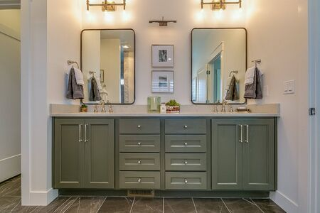 Lovely dark green bathroom cabinets and two mirrors