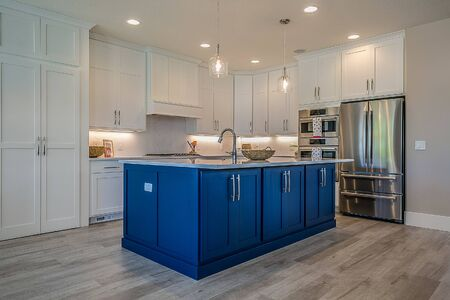 Beautiful white kitchen and island with blue cabinets