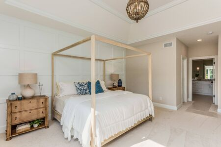 Beautiful canopy bed in white master bedroom with wainscoting walls Archivio Fotografico