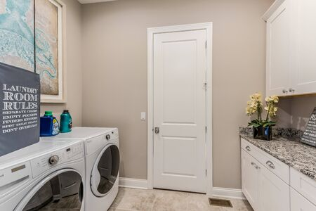 Clean and bright laundry room with white cabinets Foto de archivo