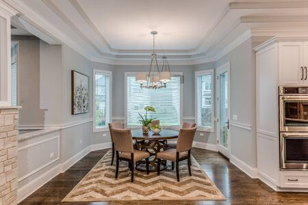 Luxury abounds with crown molding, wood cased windows and recessed ceiling in dining room