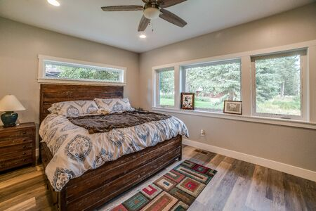 Good size master bedroom with hardwood floors and linear window above the bed Banque d'images