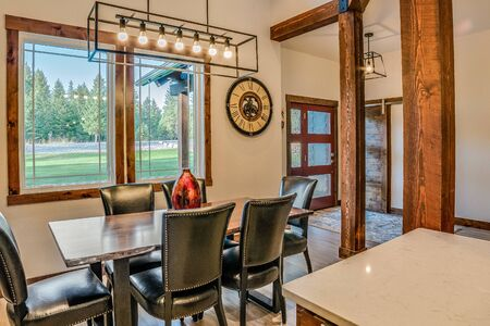 Dining area next to kitchen surrounded by wood beams