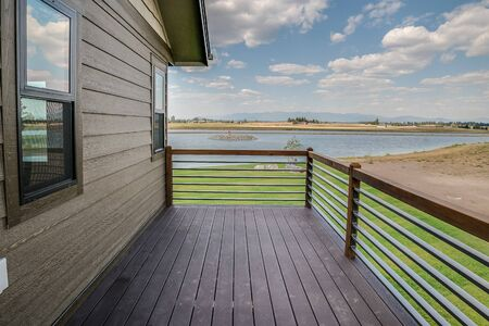 Beautiful deck with view of open green space and lake Foto de archivo