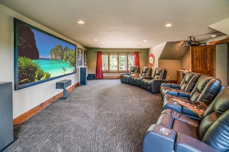 Theater room with large projection screen and plenty of seating for a crowd
