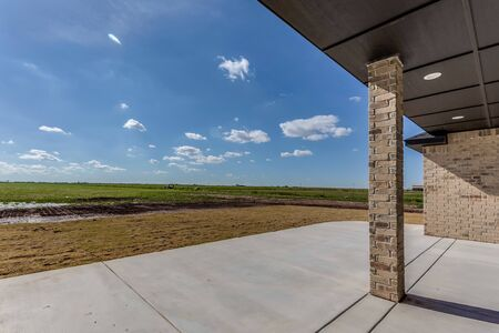 Open back patio with a view of open fields