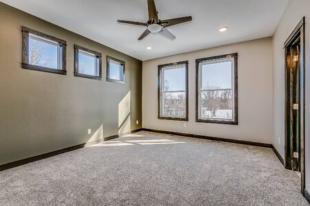 Empty bedroom with lots of windows giving natural light