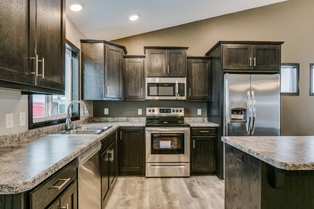 Kitchen with dark wood cabinets and vaulted ceiling