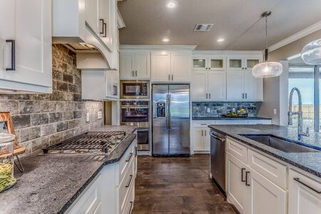 Upgraded kitchen with double ovens and white cabinetry