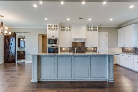 View of kitchen with island and white cabinets