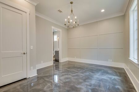 Empty room with sealed flooring and wainscoting walls