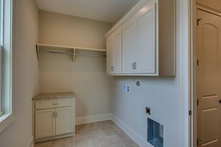 Laundry room with white cabinets and no washer and dryer yet
