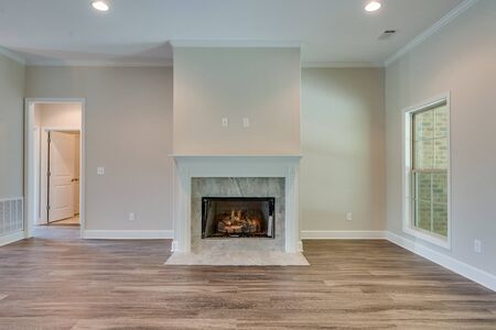 Empty family room with a fireplace central to the room Standard-Bild