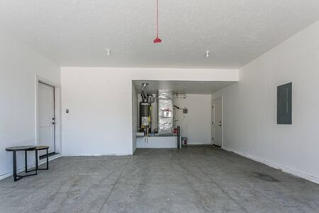 Empty garage with water heater and utility in background