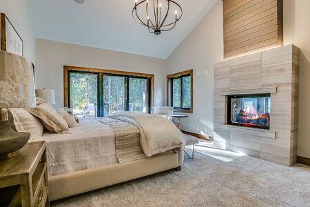 Beautiful primary bedroom with fireplace you can see through to bathtub