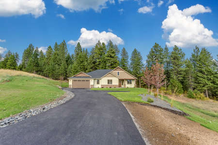 Long asphalt driveway leading to newly built home in Idaho
