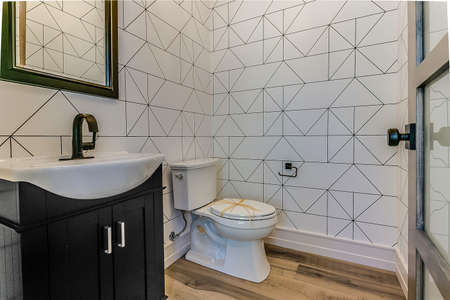 Big powder room with unique sink and decorative wallpaper