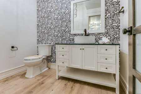 Big powder room with vessel sink and decorative wallpaper
