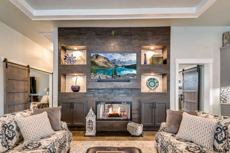 Great family room with fabulous dark colored fireplace with built-in shelves Archivio Fotografico