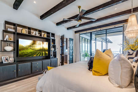 Wood beam ceiling and glass door to the exterior compliment this lovely large parents bedroom