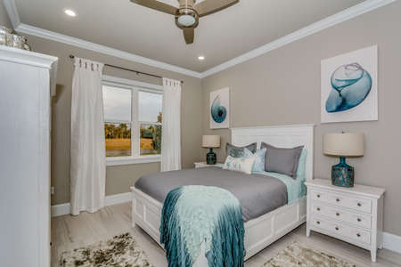 Beautifully decorated bedroom in model home with much detail and trim