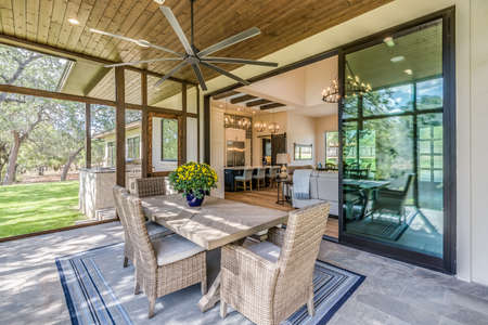 Large covered patio with gorgeous tinted glass sliding doors opening up wide for airflow