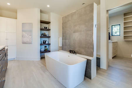 Beautiful rectangle-shape free standing bathtub in the center of the bathroom in a luxury home