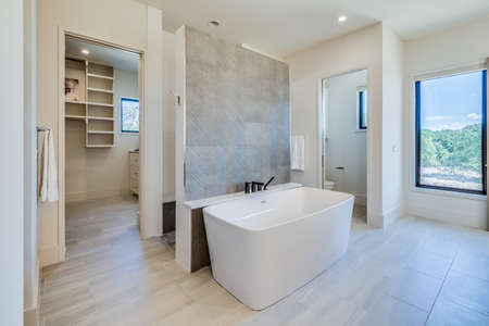 Beautiful rectangle-shape free standing bathtub in the center of the bathroom in a luxury home Archivio Fotografico