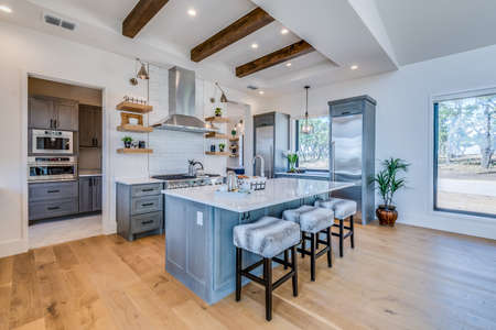 Exquisite kitchen with large island and tray ceiling with wood beams