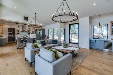 Amazing open concept family room and dining area with two large circle chandeliers adding distinction to a spacious home