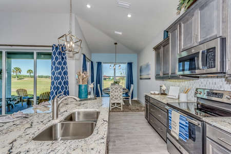 View of kitchen with island and gray cabinets. Imagens