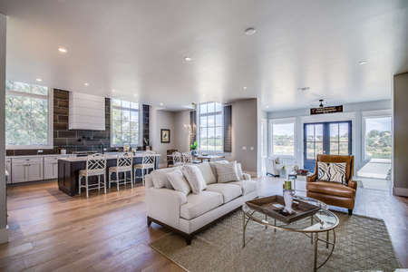 Shiplap walls and wood flooring with white couch in family room
