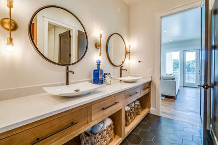Round mirrors and double vessel sinks add beauty to bathroom