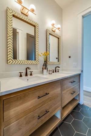 Beautiful decorative tile flooring and natural wood cabinets with elegant separate mirrors 写真素材
