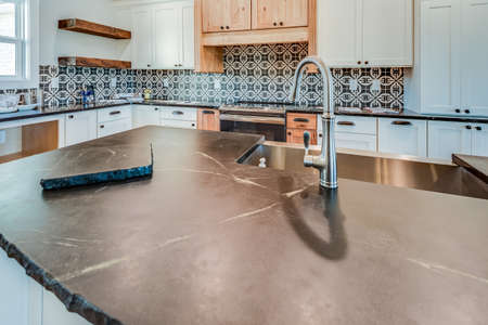 Dark stone countertop with decorative tile backsplash in extraordinary kitchen.