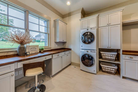 Laundry room with white cabinets and washer and dryer .