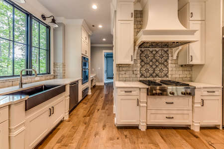 View of kitchen with island and white cabinets.