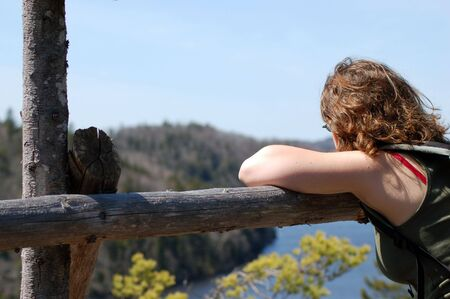 Girl daydreaming at a look off at the top of a hiking trail