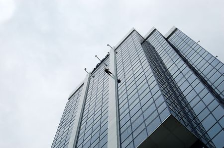 Woman rappeling down a skyscraper. Stock Photo