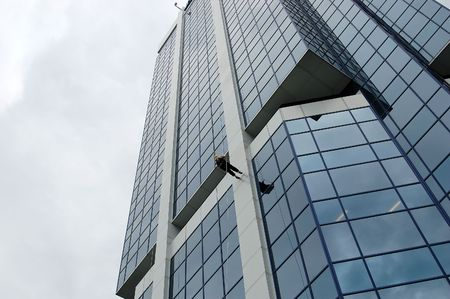 Woman rappeling down a skyscraper. photo