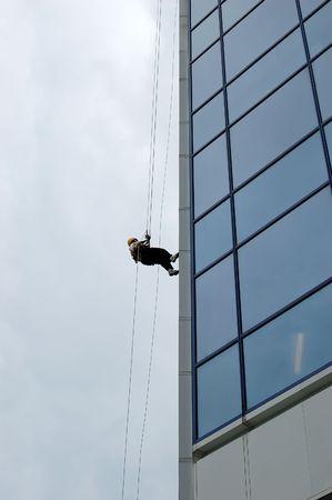 Femme rappeling en bas dun gratte-ciel.