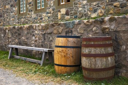 documented: A bench and two barrels along side stone walls Stock Photo