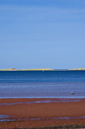 The beautiful red sands of Prince Edward Island and the blue ocean and sky Stock Photo