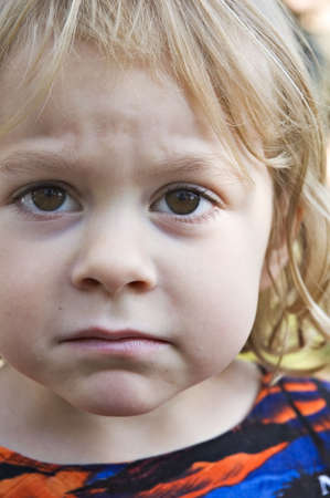 A cute toddler posing with a sad expression Stock Photo