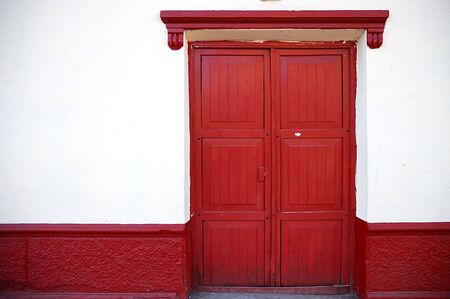 Red door, White Wall on a colonial style building in Puno, Peru Stock Photo