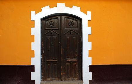 Black door, Yellow Wall on a colonial style building in Puno, Peru
