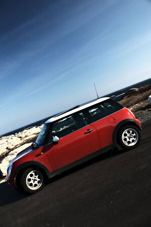 Red Mini Cooper with rich blue ocean and sky Editorial
